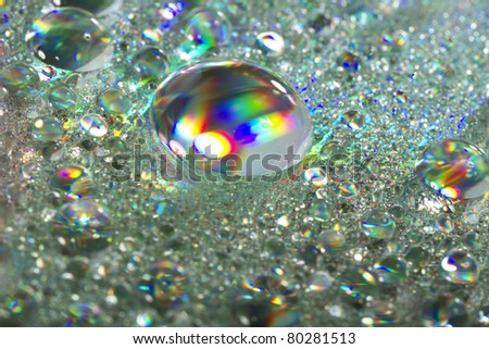 Close up view of many colorful and bright drops of water on a shiny surface. - stock photo