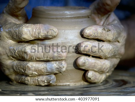 Close-up view of master working on pottery wheel and making clay pot - stock photo