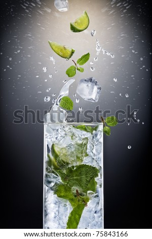 Close up view of mojito cocktail on black background - stock photo