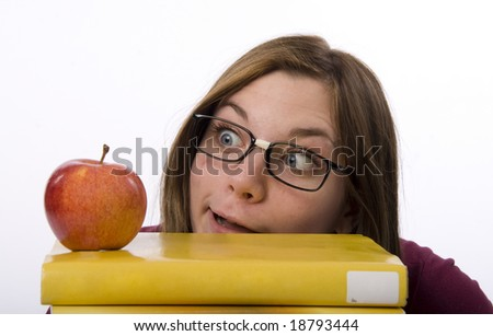 Close-up view of nerdy female student looking at apple. - stock photo