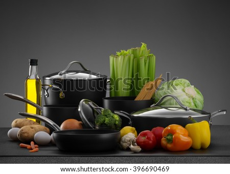 close up view of nice cookware set with some vegetables on grey back - stock photo
