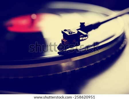 Close up view of old fashioned turntable playing a track from black vinyl toned with a retro vintage instagram filter effect app or action  - stock photo