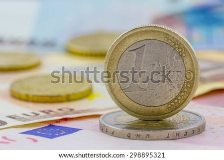 Close-up view of one Euro coin on banknotes background - stock photo