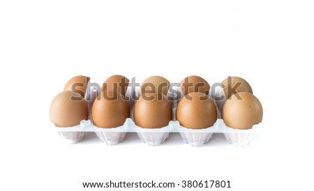 Close-up view of organic Brown Eggs on Plastic Egg Carton isolated on white background. Selective focus and shallow DOF. Copyspae. Panoramic style. - stock photo