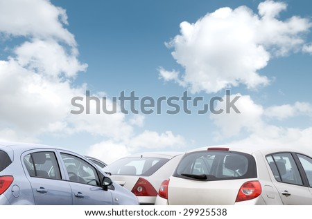Close-up view of parked cars with cloudy blue sky - stock photo