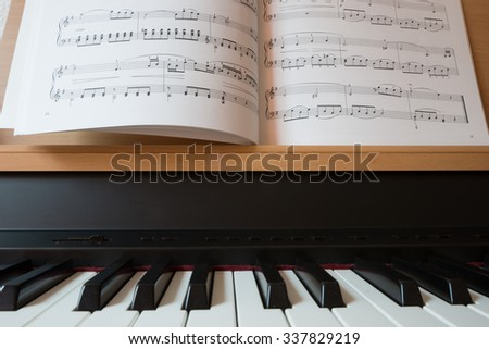 Close up view of piano keyboard and music book - stock photo