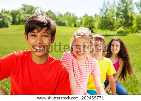 Close up view of positive boy and friends behind - stock photo