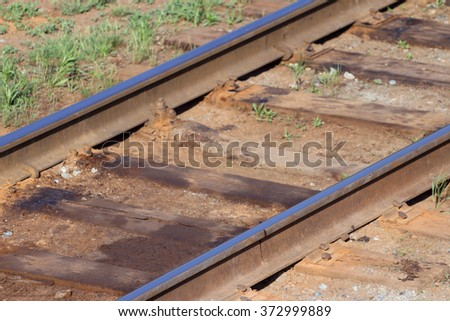 Close up view of railway with wooden sleepers and green grass - stock photo