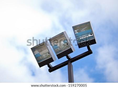 Close up view of Recreation Center Flood Lights Blue Sky - stock photo