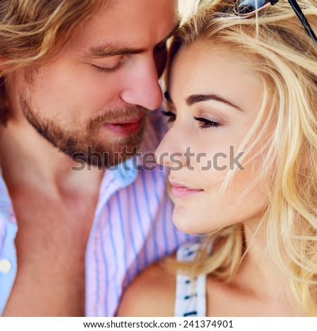 Close up view of romantic couple at beach on holidays. Attractive man and beautiful woman fall in love .