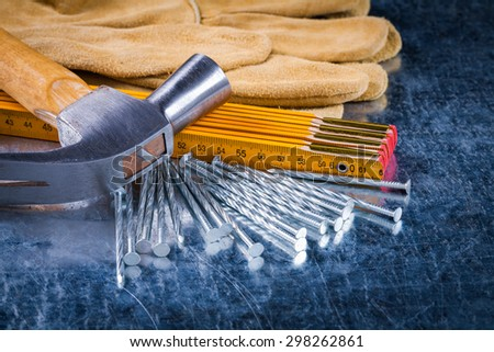Close up view of safety construction gloves nails wooden measuring meter and claw hammer on scratched metallic background building concept. - stock photo