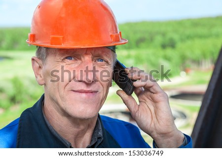 Close-up view of senior manual worker in orange hardhat calling on the phone - stock photo