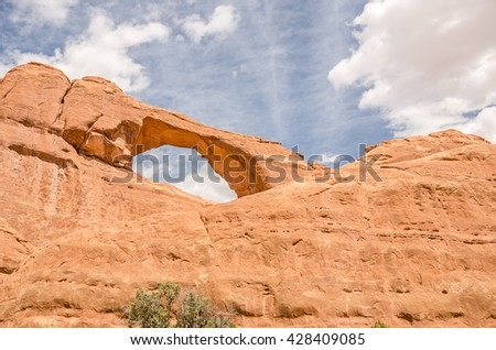 Close-up view of Skyline Arch with beautiful, fluffy clouds in Arches National Park near Moab, Utah - stock photo