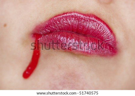 Close up view of some strawberry syrup on red lips.