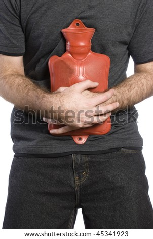Close-up view of somebody holding a hot water bottle to soothe their sore stomach - stock photo