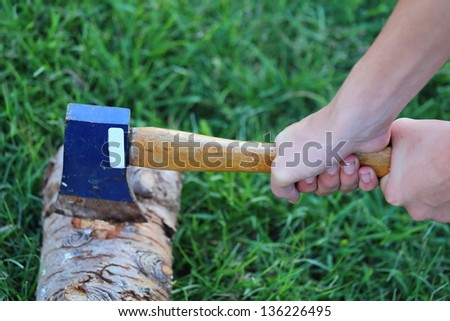 Close up view of someone using a hatchet with both hands to cut through a log - stock photo