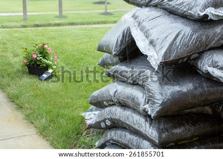 Close up view of stacked plastic bags of commercial organic mulch from a nursery for garden maintenance in spring standing in rain with potted flowers on the grass behind - stock photo