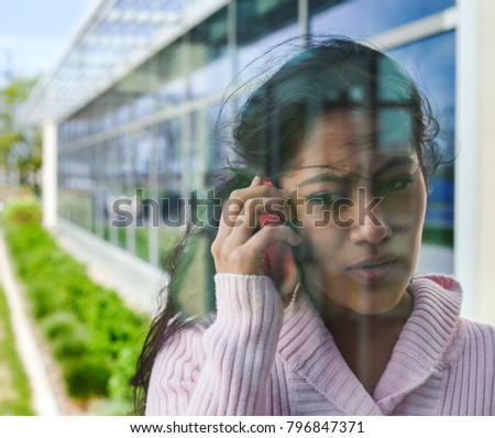 Close-up view of student face talking on mobile through window