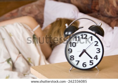 Close up view of table clock and woman sleeping  - stock photo