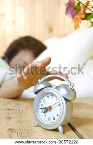 Close up view of  table clock and woman sleeping on back - stock photo