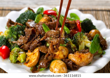 Close up view of tender beef slices, mushrooms, broccoli, peppers and peas in white plate. Selective focus on single piece held by chopsticks.