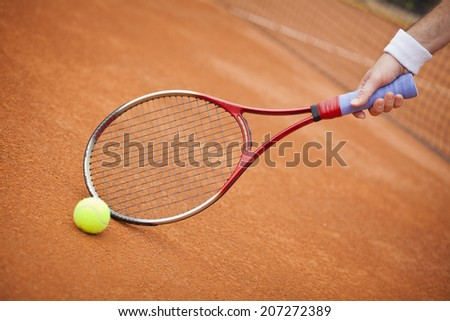 Close up view of tennis racket  and ball