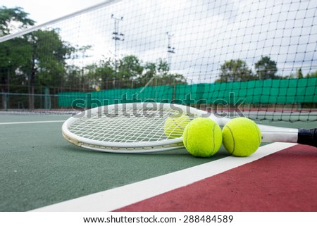 Close up view of tennis racket and balls on the tennis court - stock photo