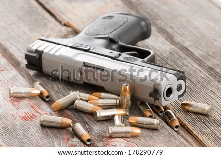 Close up view of the barrel of a handgun with scattered bullets and cartridges lying on old rustic wooden boards depicting violence, crime and robbery with copyspace - stock photo