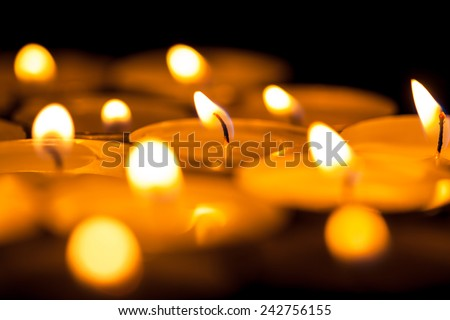 Close up view of the candles cutting through the darkness.  - stock photo
