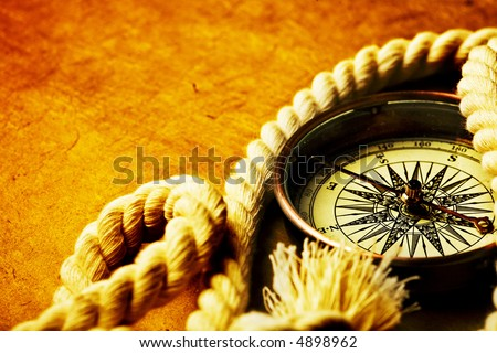 Close up view of the compass on old paper background - stock photo
