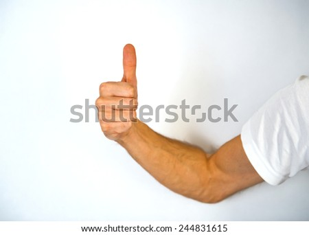Close up view of the hand of a man giving a thumbs up gesture of approval and success with his knuckles towards the camera and arm extended from the side, isolated on white - stock photo
