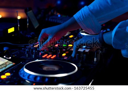 Close up view of the hands of a male disc jockey mixing music on his deck with his hands poised over the vinyl record on the turntable and the control switches at night - stock photo