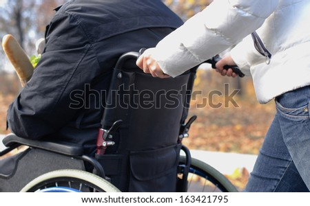 Close up view of the hands of a woman pushing a disabled man in a wheelchair along a rural street in the sunshine - stock photo
