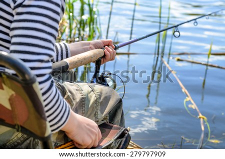 Close up view of the hands, rod and reel of a young boy sitting in a chair fishing at a tranquil lake - stock photo