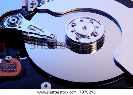 Close-up view of the opened hard disk drive(toned in blue mode) - stock photo