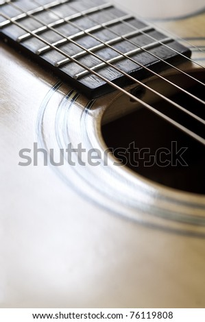 Close up view of the strings and body of an acoustic guitar. - stock photo