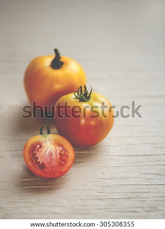 Close-up view of three vibrant, juicy tomatoes on rustic, wooden table, shallow DOF