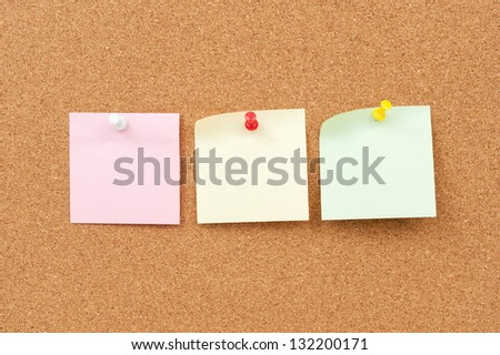 close up view of thumbtack and note paper group on corkboard - stock photo