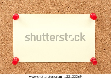 close up view of thumbtacks and note pinned on corkboard - stock photo