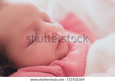 Close-up view of tiny newborn baby sleeping and cuddling.