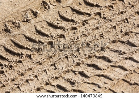 Close up View of Tire Tracks Prints in Sand on a Beach - stock photo