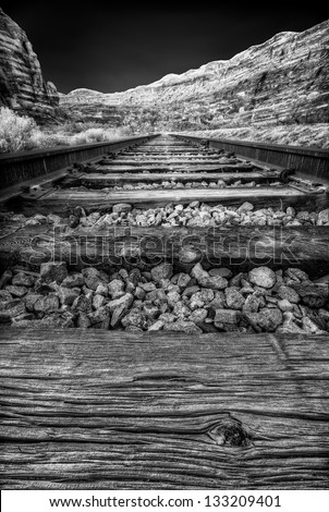 Close up view of train tracks converging toward cliffs along Long Canyon Road, Utah, USA - stock photo
