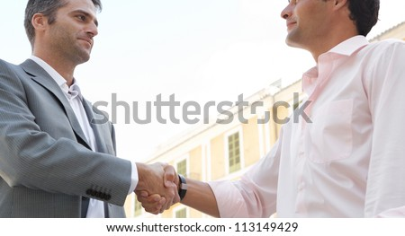 Close up view of two businessmen shaking hands while standing in front of a classic European building, outdoors. - stock photo