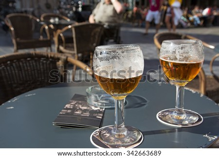 Close up view of two glasses of Belgian beer standing on the table on pub front garden. All potential trademarks are removed. - stock photo