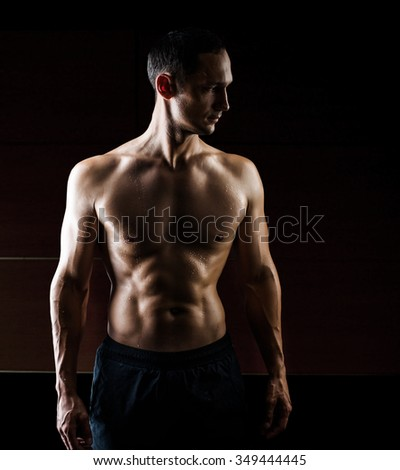 Close up view of very muscular handsome sexy man isolated on black background, naked torso - stock photo