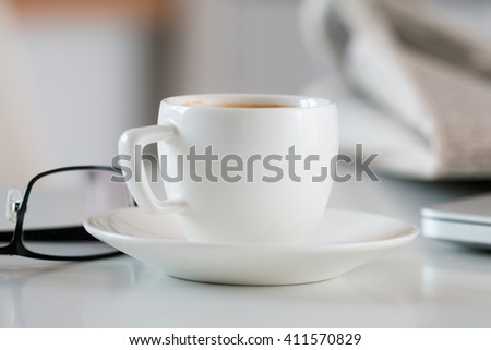 Close up view of white coffee cup on table with glasses and newspaper on background. Reading morning news concept. - stock photo