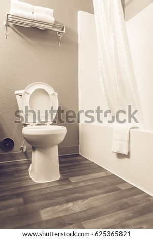 Close-up view of white flush toilet bowl with bathtub, folded towels tray, shower curtain, tub and shower combo. Modern bathroom interior with wooden floor in America.