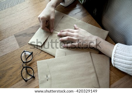 Close-up view of woman hands with envelope, glasses, in cafe