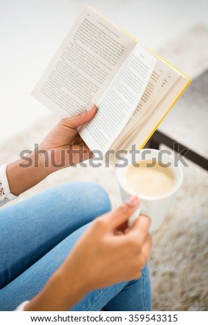 Close up view of woman holding cup of coffee and book at home