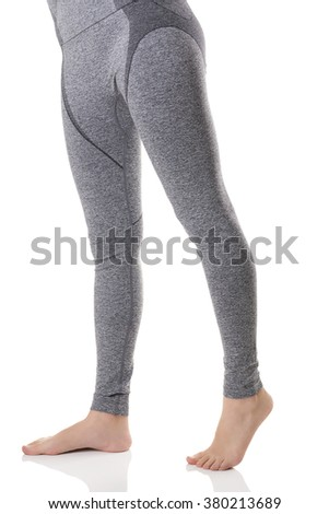 Close up view of woman legs from front side in gray sports thermal underwear with pattern on white background.                              - stock photo
